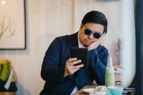 bored looking guy holding tablet in a bar